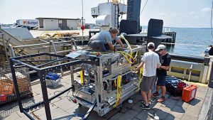 WHOI mechanical engineer Kaitlyn Tradd sits on the new towed vehicle Deep-See