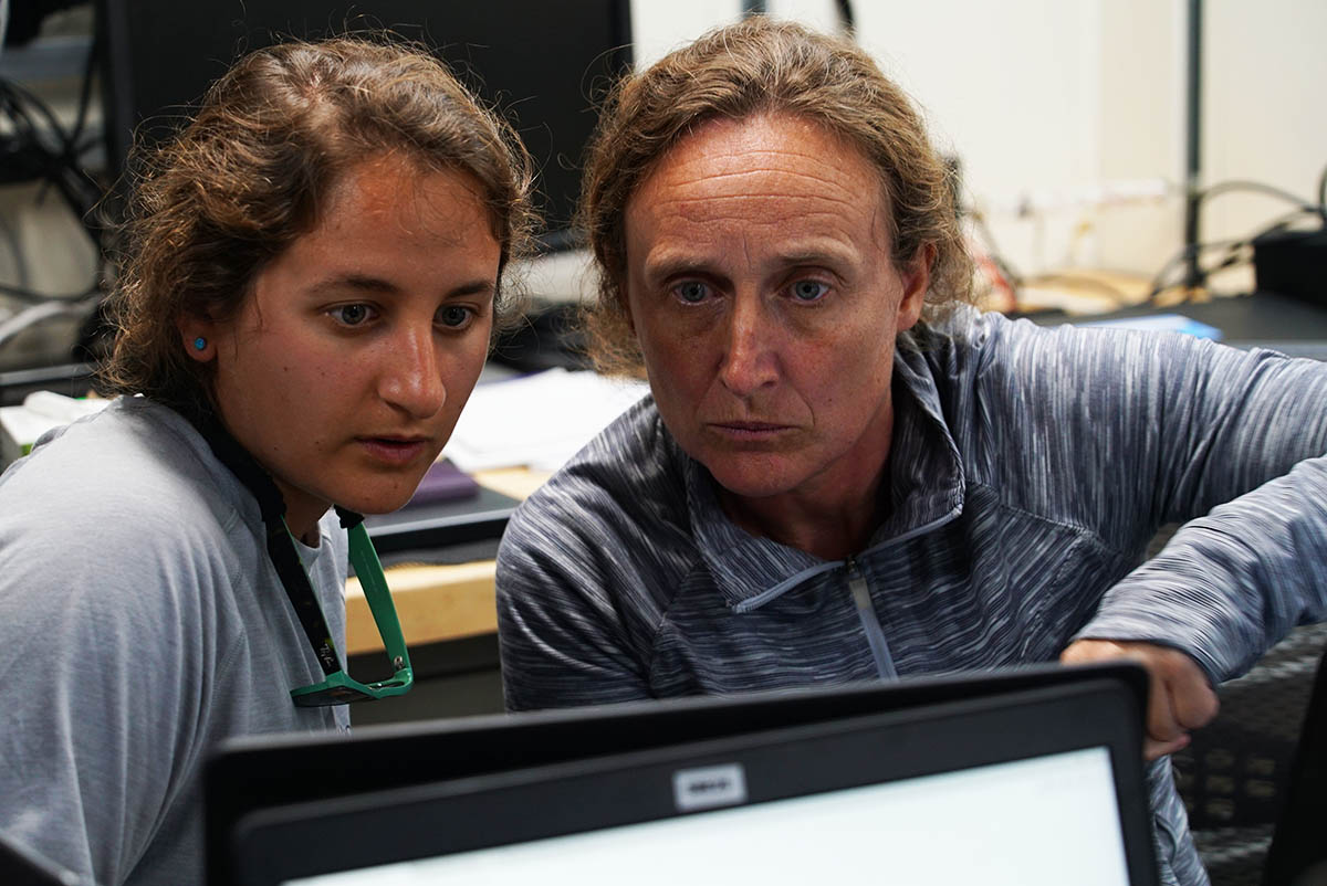 Scientist and student look at data on computer at sea