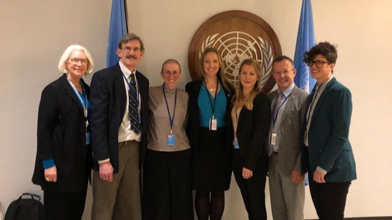 WHOI researchers in front of the seal of the United Nations