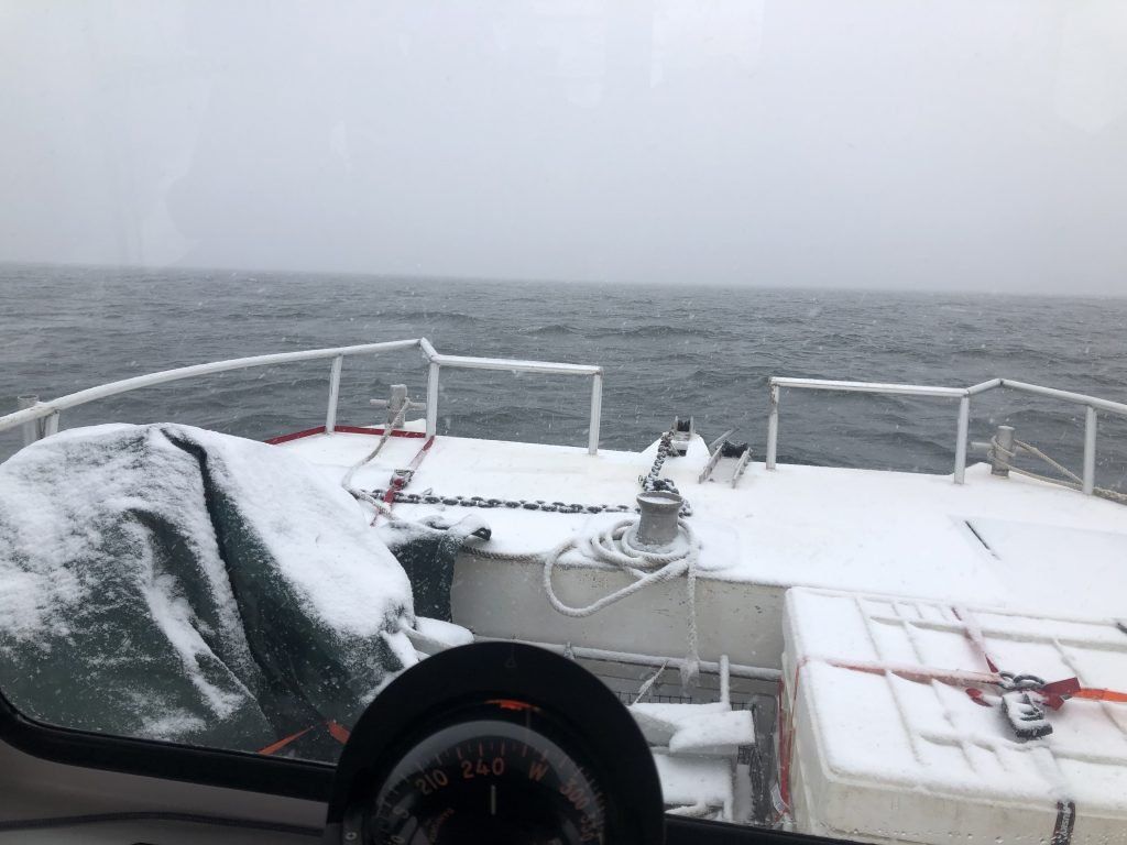 Dusted with snow from an approaching winter storm, the <em>R/V Catapult</em> motors into into Buzzards Bay with <em>Mesobot</em> stowed safely aboard.