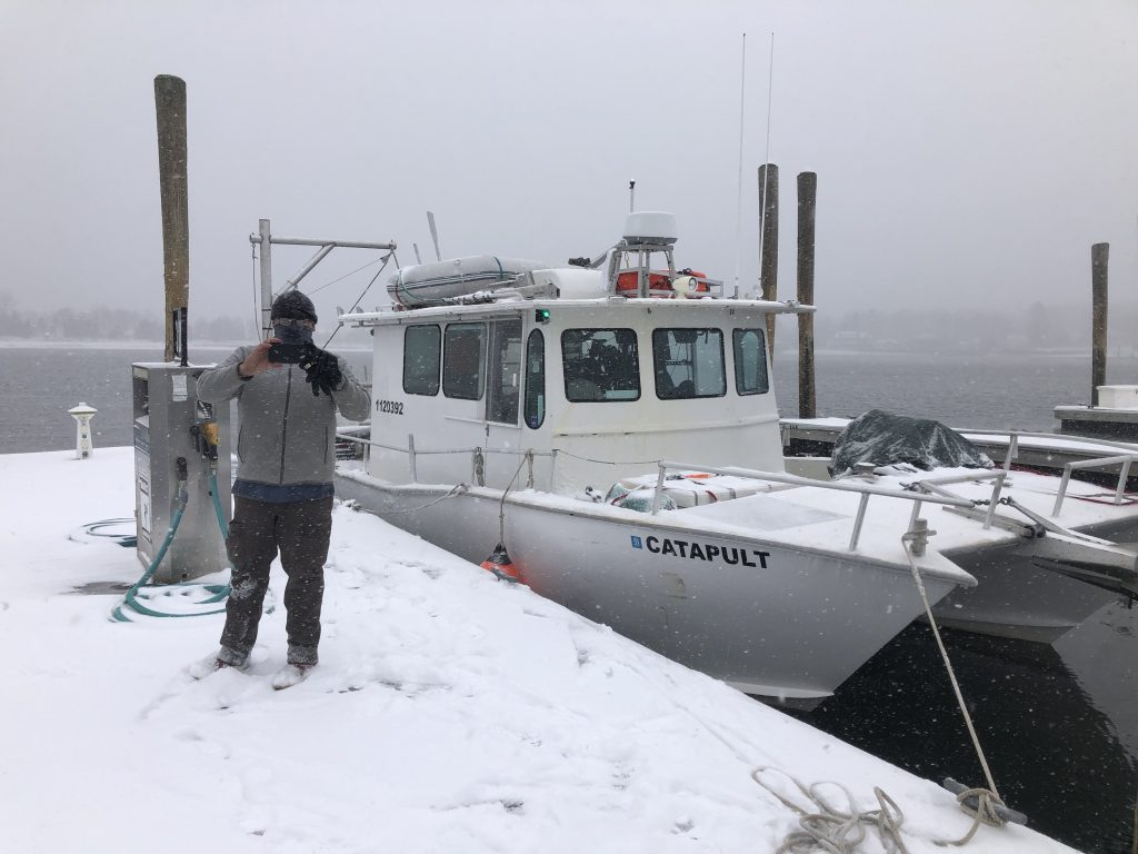 The  <em>R/V Catapult</em>, a  35-foot catamaran that the OTZ team will use for shore operations in Bermuda, sits at the dock in Woods Hole before setting sail into gently falling snow.