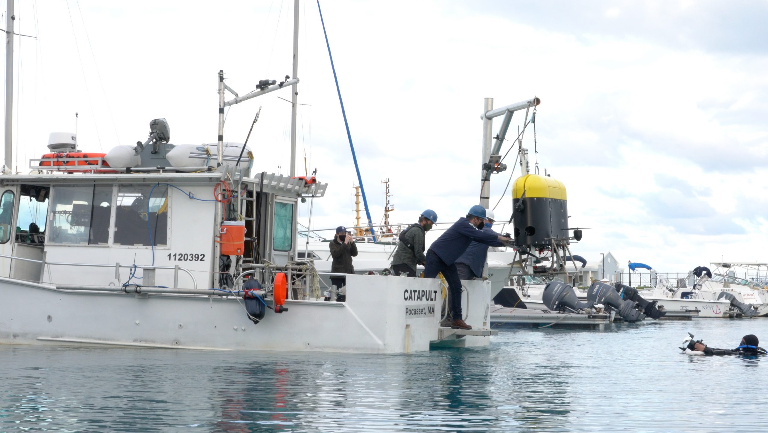 Docked at a marina, engineers Jordan Stanway and Fredrick Marin guide Mesobot into the water for testing in saltwater as engineer and underwater videographer Evan Kovacs captures the moment from the water.