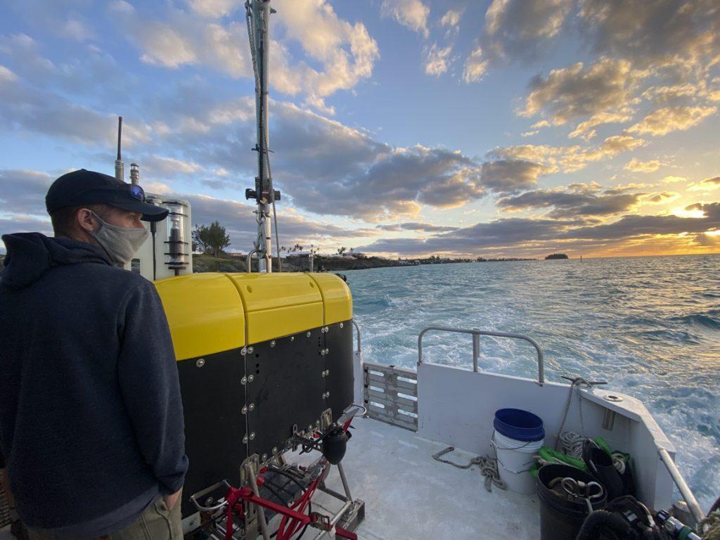 WHOI Marine ecologist Joel Llopiz admires the sunset over Bermuda's azure waters while standing next to <em>Mesobot</em> on <em>on <em>Catpult</em>'s stern. Credit: Jennifer Berglund