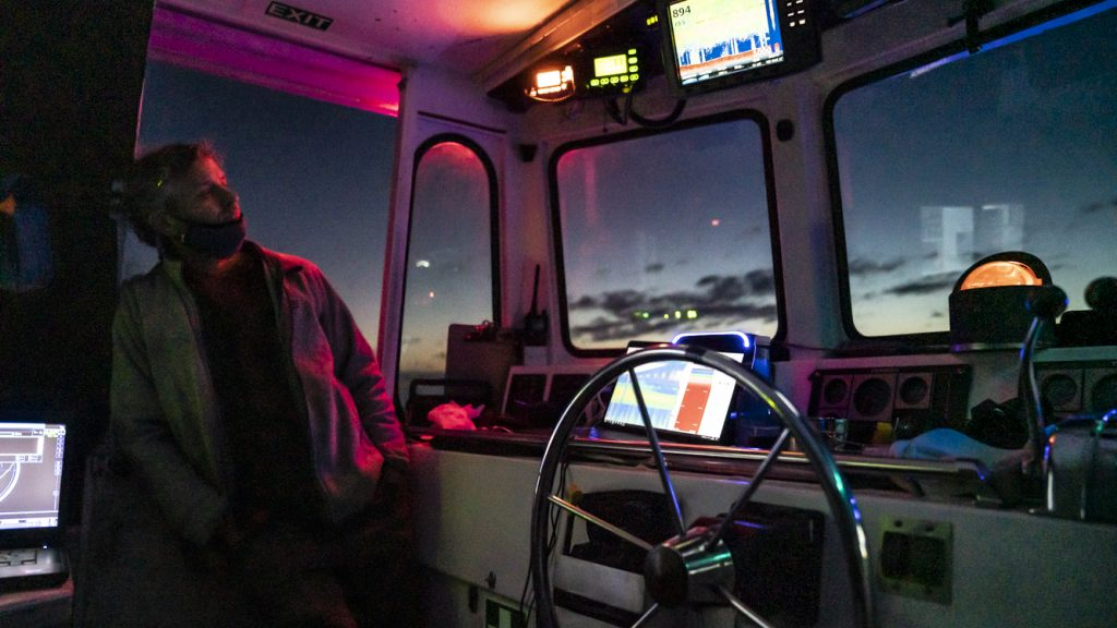 In a rare moment of calm, Evan Kovacs takes a breath to admire dusk from <em>Catapult</em>'s helm. Red lighting is used aboard the ship to limit interference from artificial light while Mesobot collects radiometer data below. Credit: Jennifer Berglund
