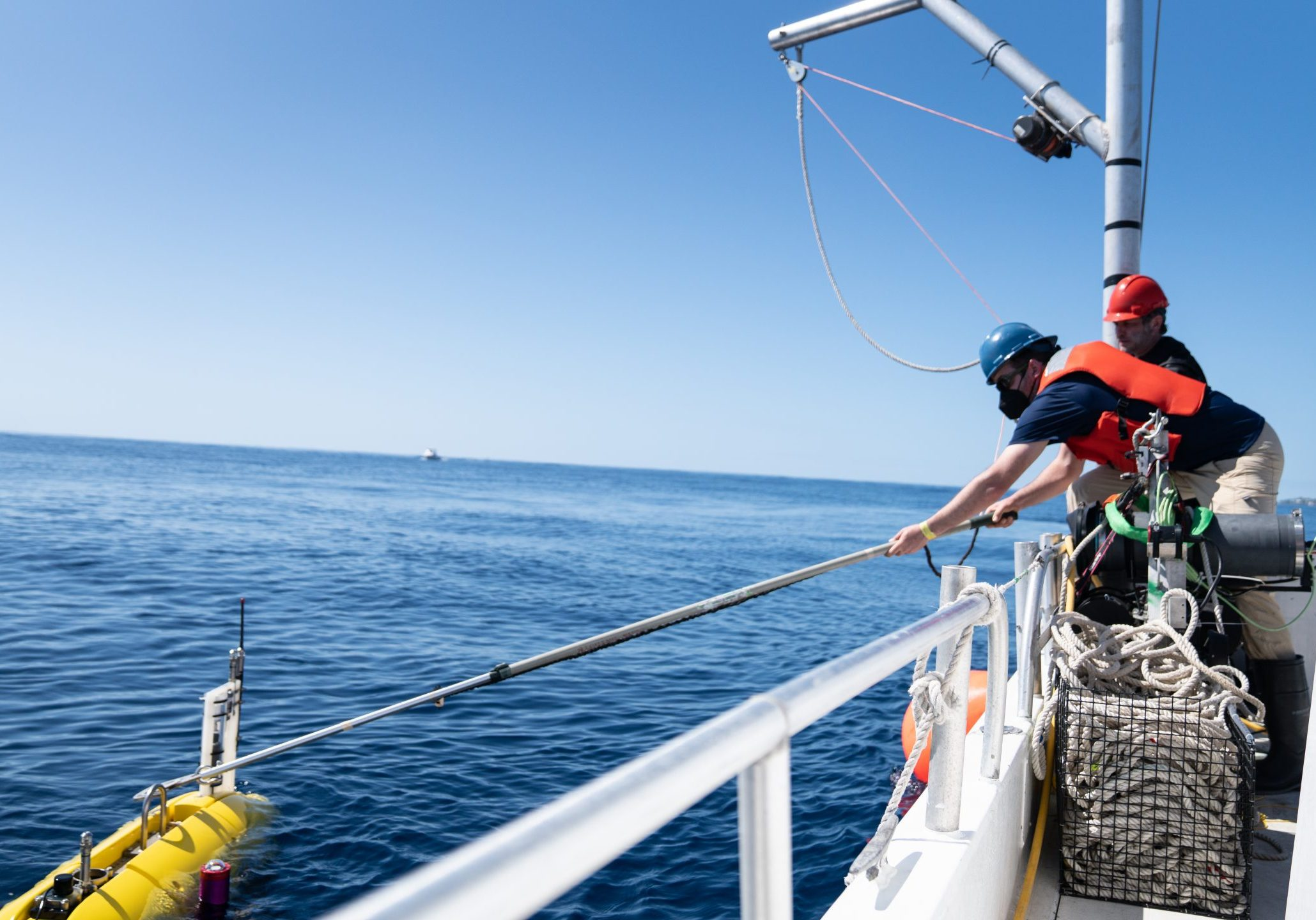Research Technician Fredrick Marin uses a pole to hook <em>Mesobot</em> to <em>Catapult</em>'s winch, which will lift it onto the deck. Credit: Jennifer Berglund