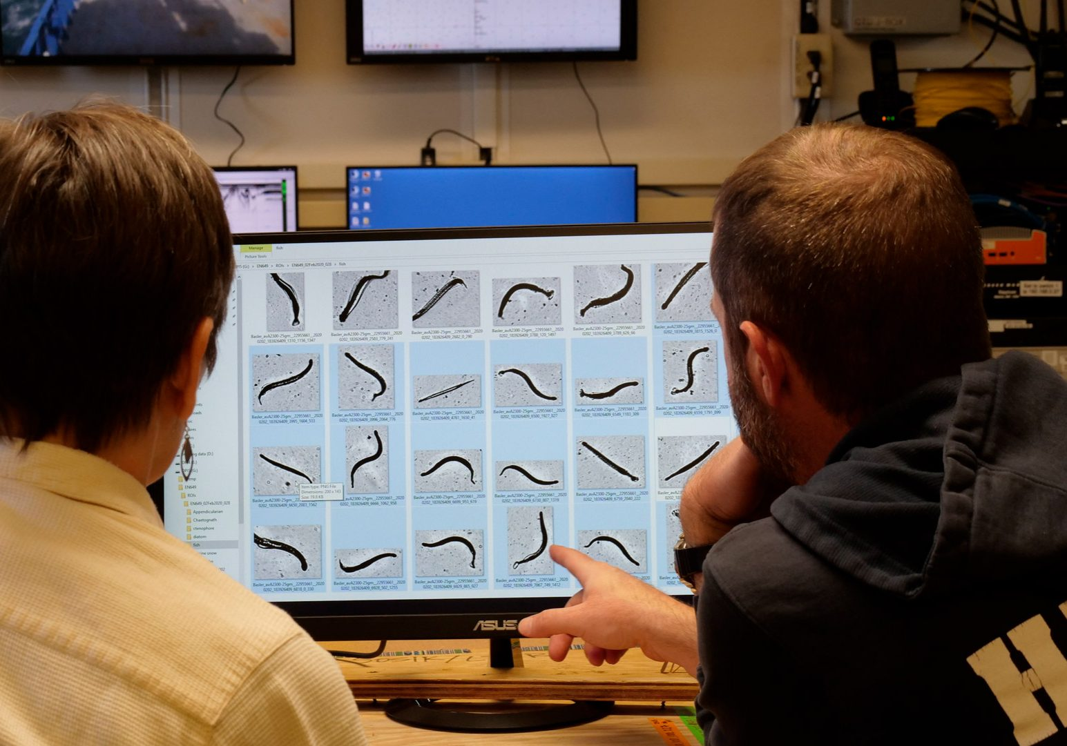 two scientists look at a computer screen with what appears to be a repeating image