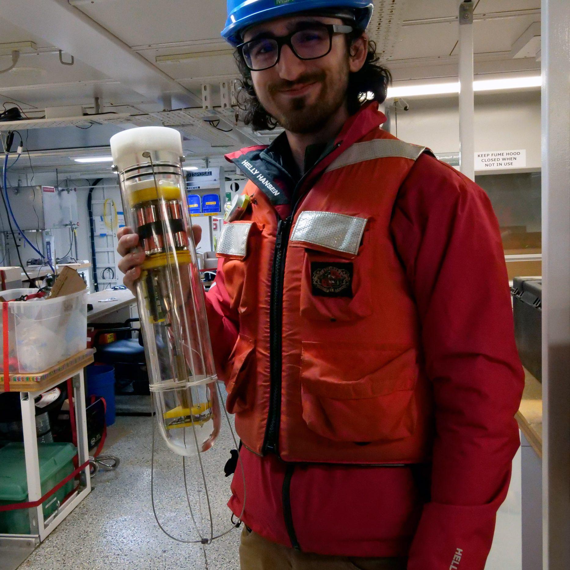 Jackson Sugar (URI) holding a prototype MINION unit. Photo by Ken Kostel, Woods Hole Oceanographic Institution.